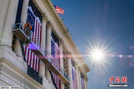 当地时间1月15日,美国华盛顿国会大厦前举行特朗普就职仪式彩排。图为工作人员现场铺设设备。