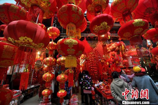 资料图:1月16日,福州民众在商铺选购各种春节饰品。随着春节临近,市民们开始忙着选购春联、中国结、红灯笼等充满喜气的年货。张斌 摄
