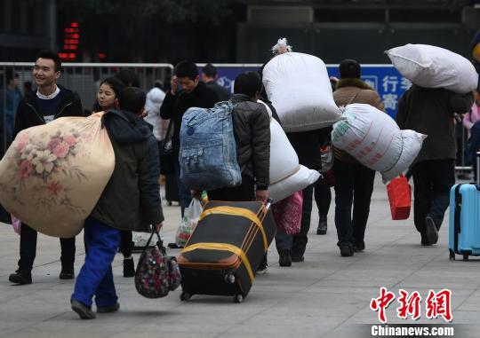 外出务工人员扛着大包行李踏上回家路。陈超 摄