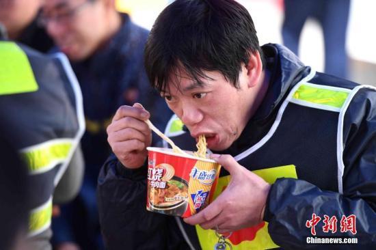 春运期间,返乡农民工吃方便面。 王东明 摄