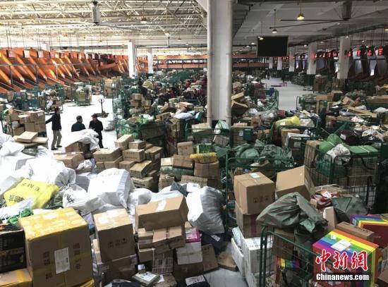 """1月20日,湖南长沙邮区中心局的工作人员正在处理堆积的快递包裹。随着中国春节的临近,为了避开实体店购物的拥挤和繁琐,越来越多的人选择网络购置年货,快递行业也随之迎来""""春运""""高峰。记者 唐小晴 摄"""