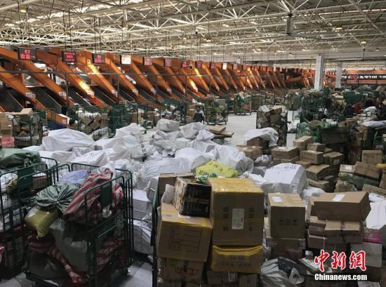 """1月20日,湖南长沙邮区中心局的工作人员正在处理堆积的快递包裹。随着中国春节的临近,为了避开实体店购物的拥挤和繁琐,越来越多的人选择网络购置年货,快递行业也随之迎来""""春运""""高峰。<a target='_blank' href='http://www.chinanews.com/'>中新社</a>记者 唐小晴 摄"""