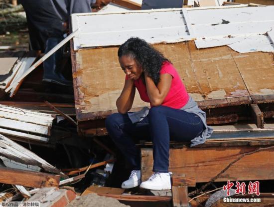 当地时间1月21日,美国密西西比州哈蒂斯堡遭遇龙卷风袭击,导致数人丧生,房屋、树木等受损严重。图为一名女子坐在自家房屋的废墟中。