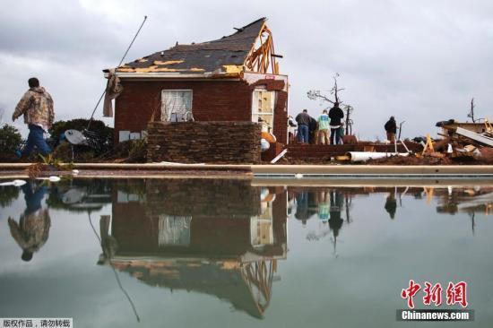 1月22日,美国佐治亚州民众在被摧毁的废墟旁。1月21日和22日,美国东南部地区遭强烈暴风雨和龙卷风席卷肆虐,已经导致至少16人死亡。