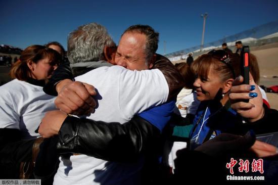 """当地时间2017年1月28日,美国与墨西哥边境举行""""拥抱,而非隔离墙""""的活动,分隔美墨两国的亲属在边境线附近短暂团聚。"""
