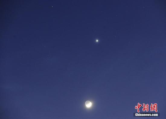 """2017年1月31日傍晚在大连市拍摄的""""双星伴月""""天象。当晚,金星、火星和月球同时出现在我国夜空中。弯月像一条小船漂荡在西南方深蓝色的天幕之上。 发 刘德斌 摄 图片来源:cnsphoto"""