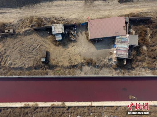 资料图:太原一家个体涂料厂颜料罐管道及自来水管道破裂,导致自来水将颜料冲至防洪渠内。韦亮 摄