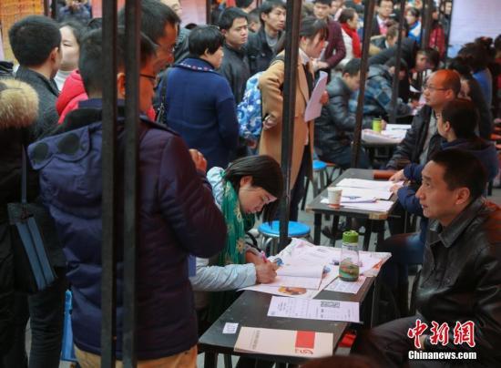 资料图:在武汉市纳杰人才市场招聘会上,挤满了前来应聘的求职者。中新社记者 张畅 摄