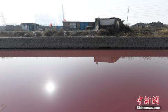 """资料图:2月4日,山西省太原市和平北路北排洪渠河道排水呈现鲜红色,施工人员使用挖掘机处理河道,阻截红色污水蔓延。附近居民介绍,这条""""红河""""持续了至少3天时间。据该排洪渠所在的太原市尖草坪区环境监察部门检查结果显示,该排洪渠为附近村庄排放生活污水所用,红色水体源头为尖草坪区柴村街办芮城村西一家个体涂料厂。因该厂颜料罐管道及自来水管道破裂,导致自来水将颜料冲至防洪渠内。据测算,事发涂料厂所在的防洪渠位置距泄洪口大约4.8公里。截至目前,太原市环保局已对红色水样进行化验,除色度超标外,未发现有毒有害特性,现尖草坪区政府已组织相关部门处理防洪渠中的红色水样。韦亮 摄"""
