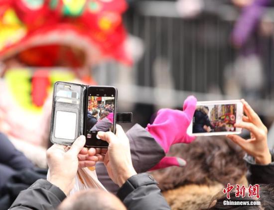 资料图:纽约唐人街,观众拍摄舞狮。<a target='_blank' href='http://www.chinanews.com/'>中新社</a>记者 马德林 摄