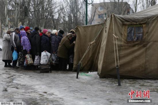 资料图:在乌克兰顿涅茨克市以北大约6公里的阿夫杰耶夫卡市居民排队领取食物。2017年1月,乌克兰东部顿巴斯冲突地区的军事行动再次升级。