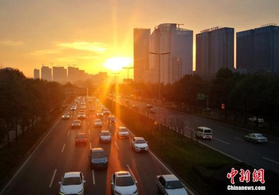 资料图:2月8日清晨,成都三环路穿行在金色阳光中的汽车。记者 刘忠俊 摄