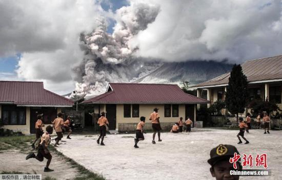 远处的火山喷出大量火山灰,小学生们仍在操场上淡定玩耍。