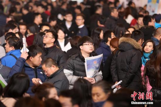 资料图:2017年2月11日,北京国际会展中心举行春季人才招聘会,求职者在招聘会寻找合适的就业岗位。中新社记者 韩海丹 摄