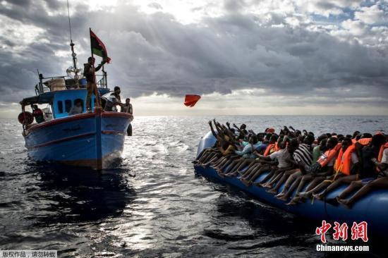 资料图:利比亚渔民向满载移民的橡皮艇上扔救生衣。 Mathieu Willcocks 摄