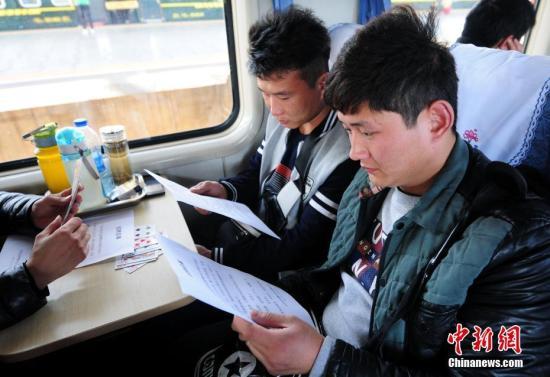 2月13日,在江西九江至广东深圳的K115次列车上,列车工作人员正在为务工旅客介绍招聘炒股配资 。胡国林 摄