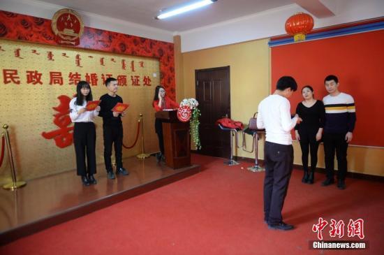2月14日,新人们在婚姻登记处排队拍照、宣誓。当天是情人节,呼和浩特玉泉区民政局婚姻登记处,不少年轻人正在办理结婚手续。据悉,当天办理结婚证人数比去年同期有所减少。<a target='_blank' href='http://www.chinanews.com/'>中新社</a>记者 刘文华 摄