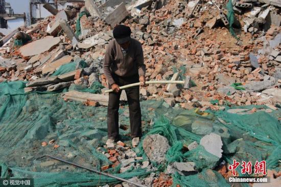 2017年2月15日,郑州西三环陇海路交叉口西侧石羊寺村拆迁工地,几名来自外地的农民工在砸钢筋或者劈砖头,钢筋每斤只能卖到0.6元到0.7元一斤。图片来源:视觉中国