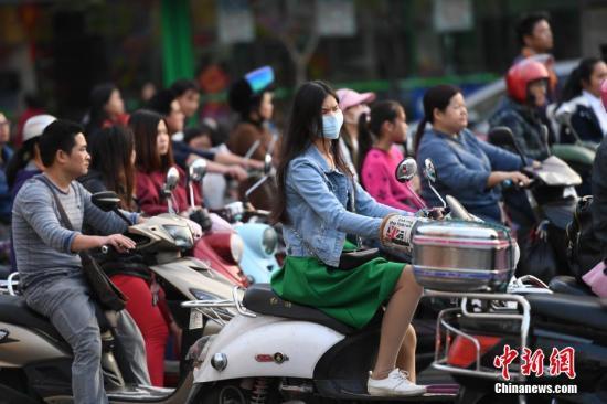资料图:市民骑电动车出行。 中新社记者 胡雁 摄