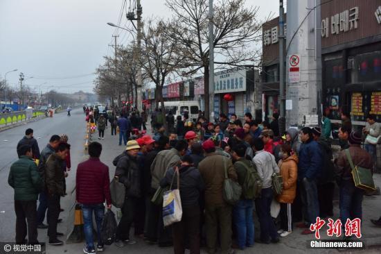 """2017年2月16日清晨,济南市二环西路与经六路延长线交汇处人头攒动,上千名农民工在此聚集""""趴活""""。这个劳务市场被称为""""济南最大自发性马路劳务市场""""。春节过后,还没有农忙的村民开始陆续返城务工。由于农民工没有技术,他们多数只能从事一些体力劳动,目前济南多数工地还未开工,""""人多活少""""现象普遍,许多民工等上一天都等不来活。 图片来源:视觉中国"""
