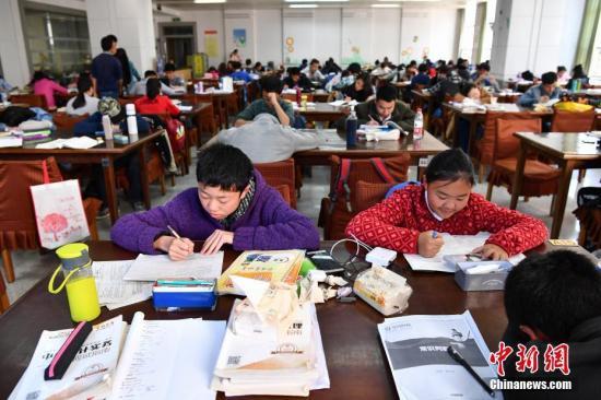 资料图:云南省图书馆自习室中随处可见写寒假作业的学生身影。 中新社记者 任东 摄