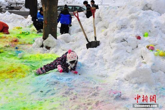 """第八届亚洲冬季运动会开幕在即,主办地日本札幌市街头大赛气氛渐渐趋浓。2月18日,札幌市中心大街的街心绿地内,特意推出一批""""冬季玩耍赛会""""项目,向路人普及冬季运动项目。图为当地儿童在彩色雪绘中乐此不疲。 记者 王健 摄"""
