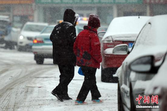图为两位老者在雪中行走。中新社记者 刘新 摄