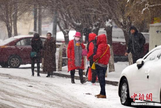 图为强降雪天气中,民众在车站等待公交车。中新社记者 刘新 摄