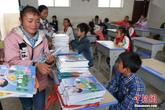 资料图:2月20日,高扒小学六年级学生在教室里领取新书。中新社记者 贺俊怡 摄
