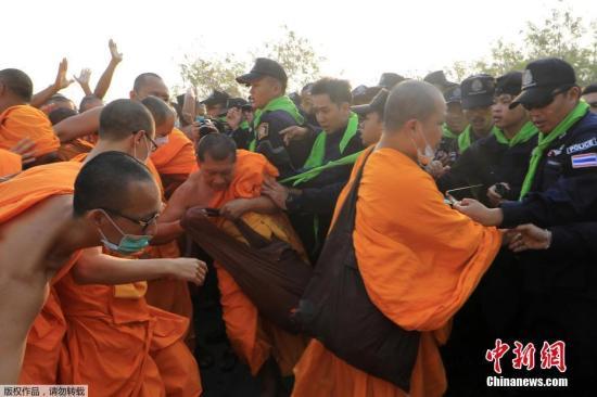 当地时间2月20日,泰国警察管控法身寺,欲逮捕涉嫌洗钱的主持。在寺庙外,众多僧侣与警察对峙。