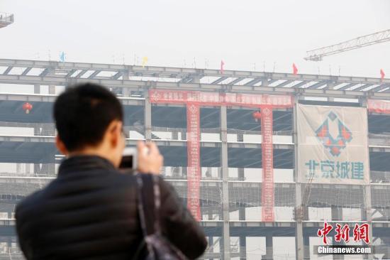 """近日,北京城市副中心建设工地一派繁忙,起重机隆隆作响。正施工的楼宇框架上,红色条幅上""""世界眼光、国际标准、中国特色、高点定位""""的词语格外显眼。以""""国际一流和谐宜居之都示范区""""为目标的副中心,正拔地而起。今年年底前,北京市委、市人大、市政府、市政协""""四套班子""""等机构将率先启动搬迁至此。这是近年来北京城市空间布局最大的一次调整。<a target='_blank' href='http://www-chinanews-com.daqiangkong.com/'>中新社</a>记者 韩海丹 摄"""