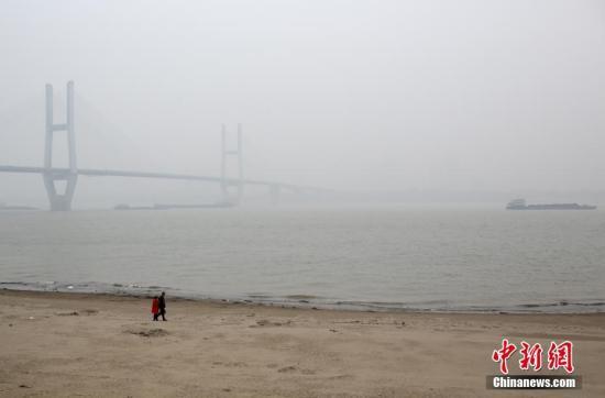 资料图 2月20日,武汉汉口江滩一对男女走在沙滩上,远处的武汉长江二桥在雾霾中若隐若现。记者 张畅 摄