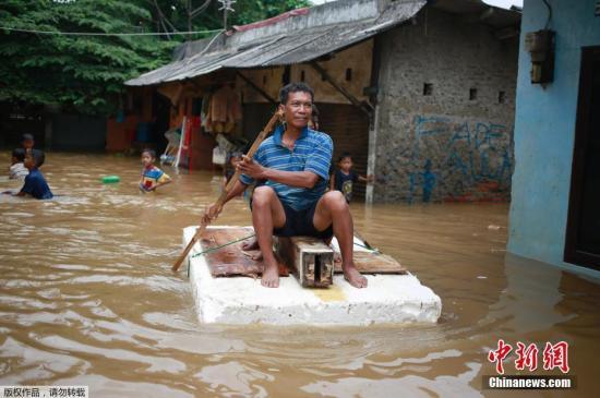 资料图:当地时间2017年2月21日,印度尼西亚雅加达在连续几小时暴雨后遭遇洪水,导致数以千计的民居被淹没,汽车搁浅,民众涉水出行。