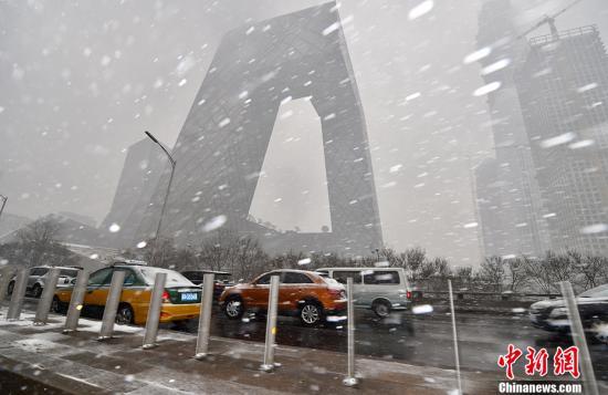 """2月21日,北京多个地区迎来降雪天气,预计降雪过程将持续至半夜。""""春雪""""如约而至,整个城市一派银装素裹的景象。图为雪中的央视大楼。中新网记者 金硕 摄"""