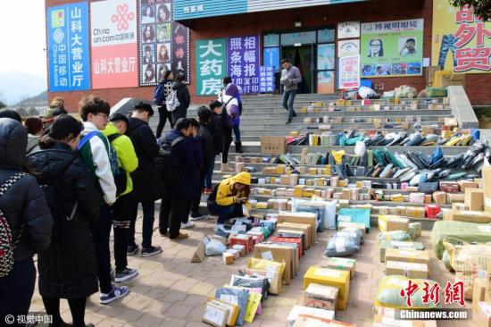 资料图:山东青岛,不少学生开学前后网购的物品陆续到达学校,快递点前取快递的同学排起长龙。图片来源:视觉中国
