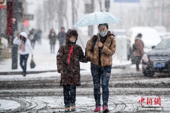 21日,太原街头,家长冒着大雪送孩子上学。 中新社记者 韦亮 摄