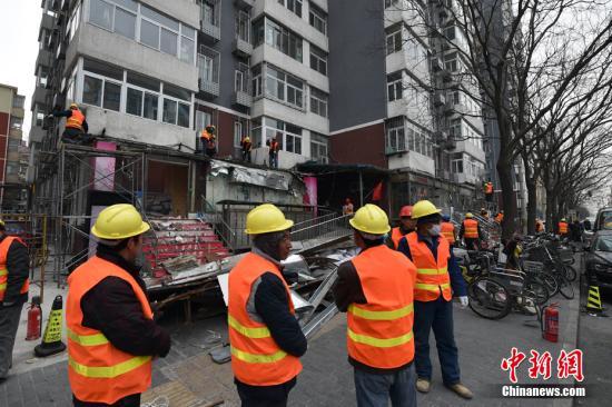 """资料图:2月21日,北京市西城区白纸坊西街上,聚集了不少工程车和执法人员,随着对大清花饭店门前避风格的拆除,拉开了白纸坊地区2017年""""开墙打洞""""整治行动的序幕。由于历史原因白纸坊西街南侧不少居民楼底墒形成了大量违法建设。金硕 摄"""