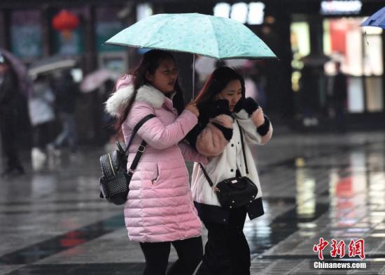 """2月22日,重庆迎来""""倒春寒"""",主城气温骤降至7℃,不少市民身着厚实冬装出行。图为重庆气温骤降,市民着厚实冬装捂耳出行。 周毅 摄"""