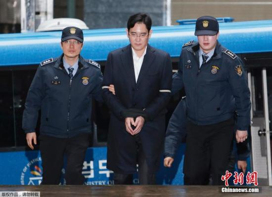 当地时间2月22日,韩国三星电子副会长李在�F(中)被押往位于首尔的特检组办公室接受问讯。三星电子副会长李在�F因涉嫌行贿、挪用公款等多项罪名于17日被捕,连日来多次接受问讯。