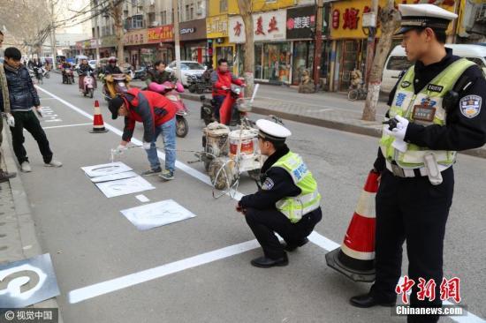 """郑州给停车位编""""身份证号"""" 防乱划停车位 。 李四信 摄 图片来源:视觉中国"""