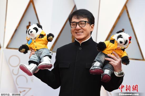 当地时间2017年2月26日,第89届奥斯卡颁奖礼(89th Annual Academy Awards)在美国洛杉矶杜比剧院举行,明星大腕云集红毯。图为成龙手举两只大熊猫玩偶亮相。