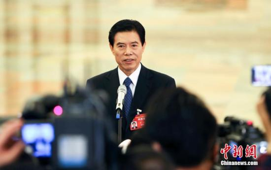 """3月3日,全国政协十二届五次会议在北京人民大会堂开幕。商务部部长钟山在""""部长通道""""接受记者采访。中新社记者 杨可佳 摄"""
