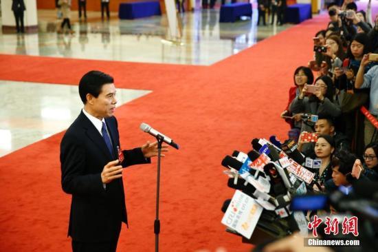 """3月3日,全国政协十二届五次会议在北京人民大会堂开幕。商务部部长钟山在""""部长通道""""接受记者采访。记者 富田 摄"""
