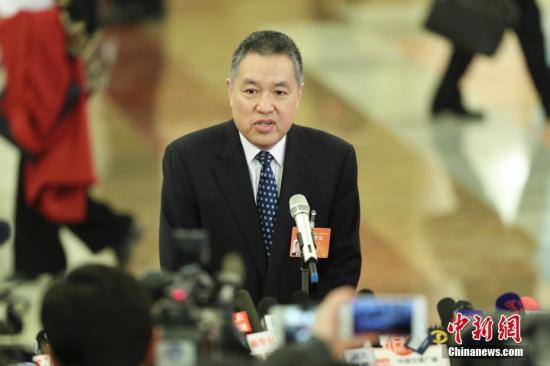 """3月5日,十二届全国人大五次会议在北京人民大会堂开幕。国家工商总局局长张茅在""""部长通道""""接受采访。记者 盛佳鹏 摄"""