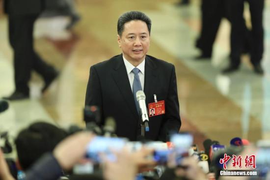 """3月5日,十二届全国人大五次会议在北京人民大会堂开幕。交通部部长李小鹏在""""部长通道""""接受采访。记者 盛佳鹏 摄"""