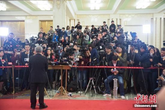 """3月5日,十二届全国人大五次会议在北京人民大会堂开幕。记者云集""""部长通道""""。中新社记者 泱波 摄"""
