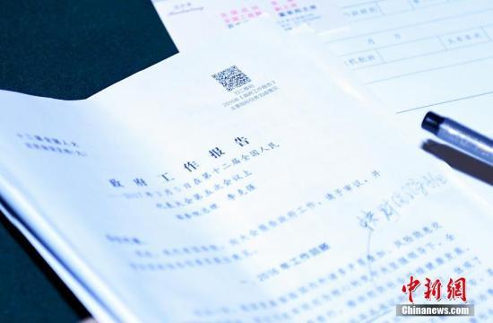 3月6日,一份摆放在政协委员桌上的政府工作报告。今年政府工作报告文本上首次印上二维码。记者 侯宇 摄