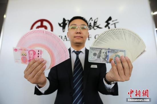 资料图:银行工作人员展示货币。张云 摄
