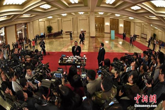 """3月8日,十二届全国人大五次会议举行第二次全体会议,""""部长通道""""受到众多记者关注。记者 金硕 摄"""