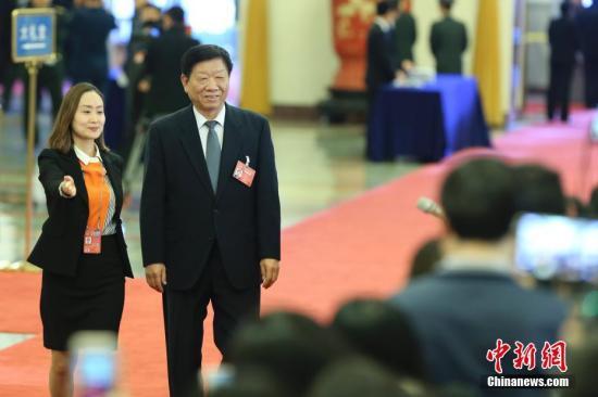 """3月8日,十二届全国人大五次会议在北京人民大会堂举行第二次全体会议。人力资源和社会保障部部长尹蔚民在""""部长通道""""接受采访。记者 盛佳鹏 摄"""